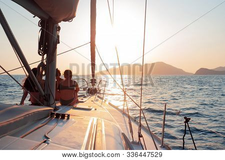 Girls Sit On The Deck Of The Yacht And Enjoy The Sunset. Boat Trip On A Yacht Under Sail, A Fragment