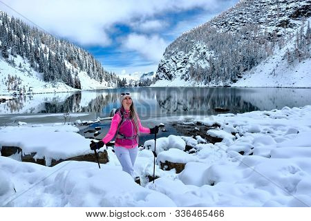 Happy Smiling Woman Snowshoeing In Snow Covered Trail By Calm Lake Agnes With Reflections Of Mountai