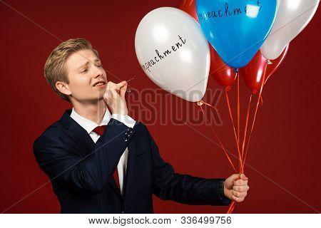 Kyiv, Ukraine - October 18, 2019: Emotional Man Imitating Donald Trump Bursting Balloons With Impeac