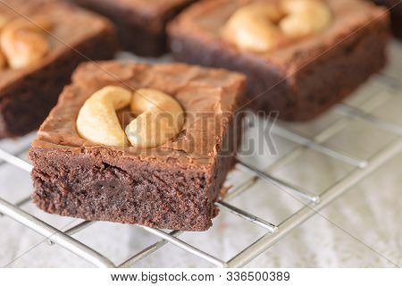 Fresh Baked Dark Chocolate Fudge Brownies. Sweet Brownie Topping With Cashew Nut Stacked On Rack. De