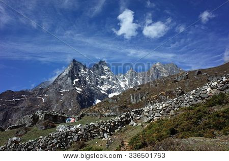 Hiking in Nepal Himalayas, Stone wall and mountain ridge of Khumuche Himal seen from the trail from Namche to Gokyo