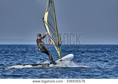 A Male Athlete Is Interested In Windsurfing. He Moves On A Sailboard On A Large Lake On An Autumn Da