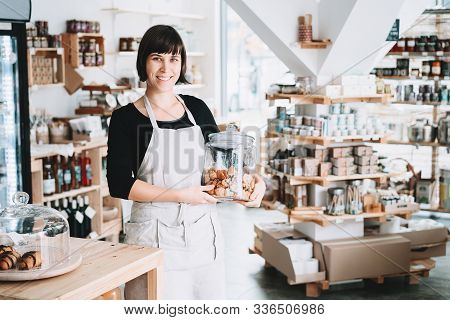 Small Local Business Owner. Seller Assistant With Glass Jar Of Pastries In Interior Of Zero Waste Sh