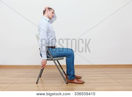 Caucasian man, sitting on chair, stretching neck - profile