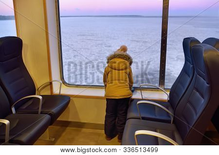 Little Inquisitive Boy Is Looking On The Window At The Amazing View Of Frozen Sea During Crossing On