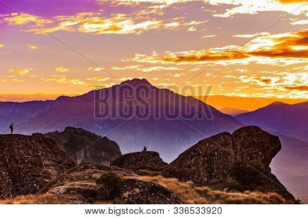 Tourists In Mountains At Sunset, Two Persons On Cliffs Rocky Formations In Thessaly Greece. Tourism