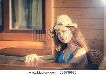 Girl In A Swimsuit On The Beach Near The Bungalow. Attractive Young Girl Sitting On The Chair At A T