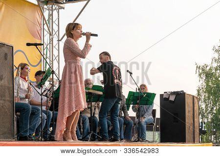 Krasnoyarsk, Russia, August 25, 2019: Female Soloist Singer In A Pink Dress Sings Outdoors, On The S