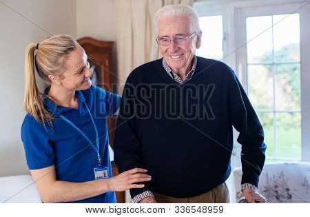 Senior Man Using Walking Frame Being Helped By Care Worker