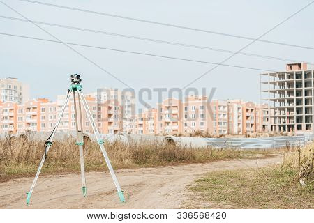 Digital Level For Geodesy Measuring On Dirt Road With Buildings At Background