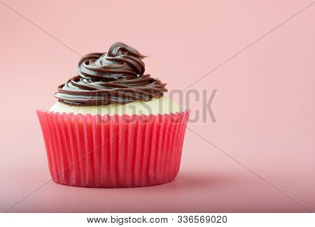 Vanilla Cupcake With Chocolate Icing In Nice Paper Mold, Pink Background