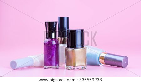 Variety Of Nail Polish Bottles With Pink Background