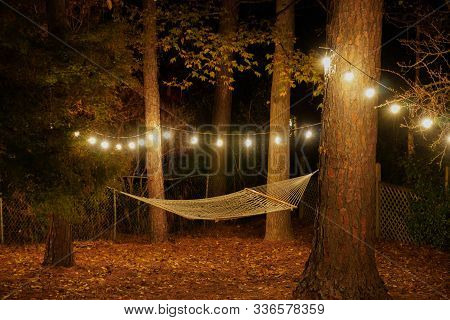 A Hammock Is Suspended Between Two Trees In A Backyard With Cafe Lights Strung Up; Romantic Nighttim