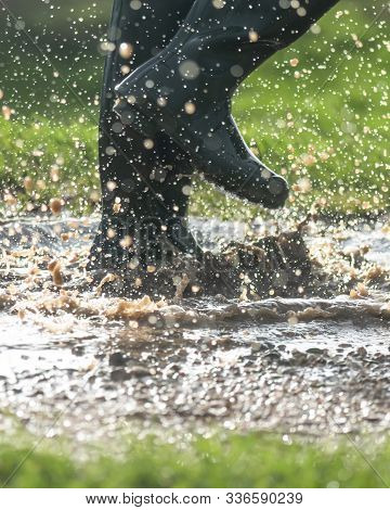 Green Welly Boots Splashing In Wet Muddy Puddles In The Early Morning Light  Copy Space At The Base
