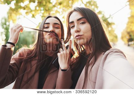 Two Cheerful And Pretty, Young Brunette Twin Girls In Casual Coat Having Fun While Taking Selfie And