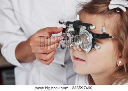 Focused Photo Of Child In Phoropter Having Testing His Eyes In The Doctors Office.