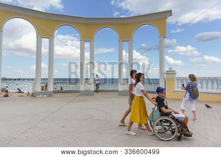 Yevpatoria, Crimea, Russia-september 07, 2019: Women With A Teenager In A Wheelchair Walk Along The