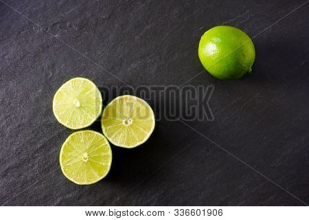 A Trio Of Green Lime Halves With A Whole Lime On A Black Slate Background