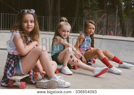 Three Young Girls Skaters Best Friends Hangout At The Skate Park On Sunset .laughing And Fun.