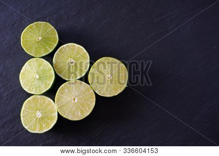 A Pyramid Of Lime Halves Pointing To The Right Where There Is Black Slate Copy Space