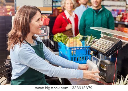 Smiling cashier at the supermarket cashier uses barcode scanner