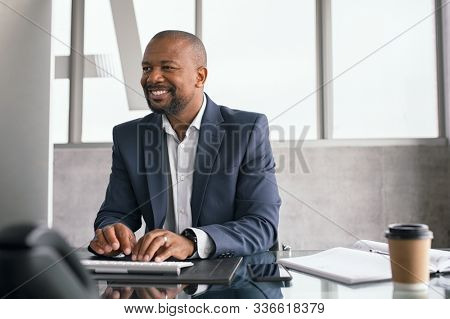 African american businessman working on his laptop. Mature business man in formal working at his desk. Smiling black middle aged man sitting in modern office working on computer and checking email.