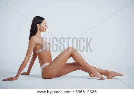 Like On The Beach. Girl With Perfect Slim Toned Young Body Sitting In The Studio With White Backgrou