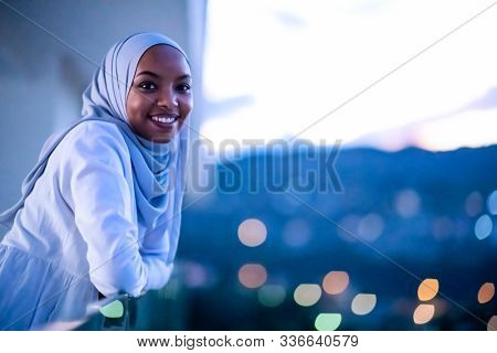 African  modern Muslim woman in night  at balcony  smiling at camera with city bokeh lights in background
