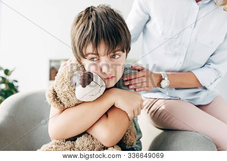 Sad Kid With Dyslexia Holding Teddy Bear And Child Psychologist Hugging Him