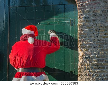 Santa Claus Is Knocking On The Old Green Door Of Gate, View From The Back.