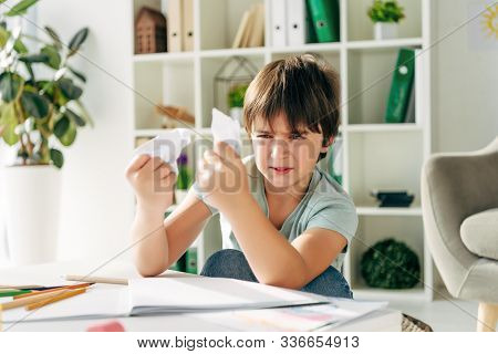 Irritated Kid With Dyslexia Holding Crumpled Papers And Sitting At Table