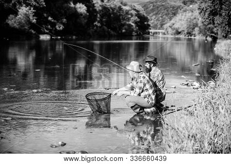 Sharing His Secrets. Experienced Fisherman Show Tips To Son. Transferring Knowledge. Men Riverside C