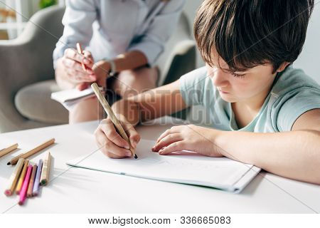 Selective Focus Of Kid With Dyslexia Drawing On Paper With Pencil