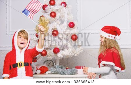 Cherished holiday activity. Kids in santa hats decorating christmas tree. Family tradition concept. Children decorating christmas tree together. Boy and girl decorating tree. Siblings busy decorating poster