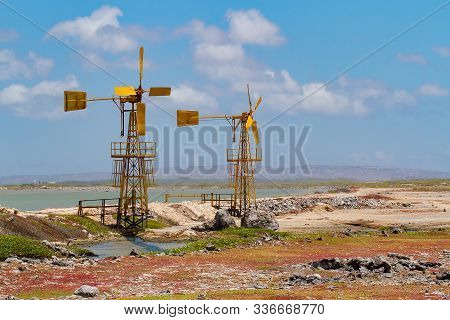 Two Yellow Windmills For Salt Extraction Near Water On Island Bonaire