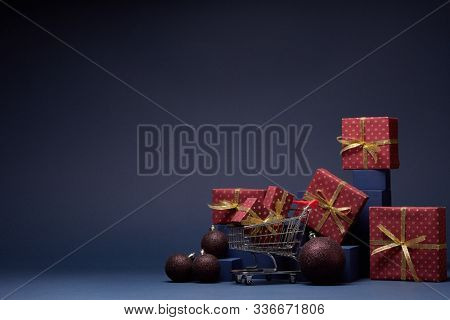 Shopping trolley, red gift boxes, fir branch and Christmas ornaments on dark blue background with copy space.  Christmas and New Year shopping. Winter sale. For design of advertising, greeting card