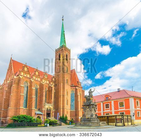 Collegiate Church Of Holy Cross And St. Bartholomew Catholic Church With Brick Tower Wall And Spire,