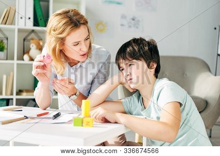 Sad Kid With Dyslexia And Child Psychologist Playing With Building Blocks