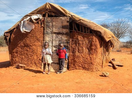 African boy and a girl in a village in  Botswana sitting in front of the hut in the dirt,  sunny day