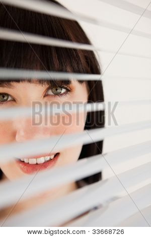 A woman smiling as she looks out through her unmoved  blinds on the window