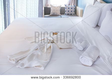 Hotel Room Service Concept. New And Clean Bathrobe, Bed Linen And Towels On The Beds.