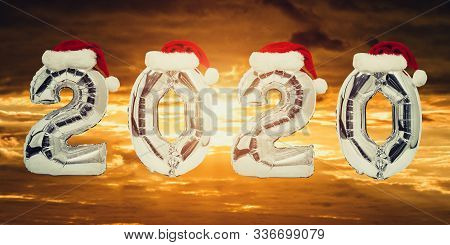Number 2020 of silvery balloons with red Santa hats. Sunset on background. New Year concept poster
