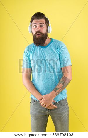 He Has True Ear For Melody. Bearded Man Listen To Music Melody. Hipster Wear Earphones Yellow Backgr