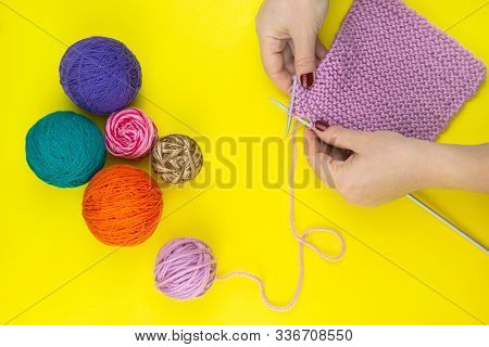 The Girl Knits A Children's Scarf On A Yellow Background
