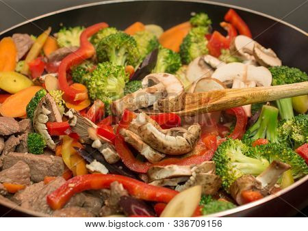 Side View Of Wooden Spoon Stirring Beef And Vegetables In Cast Iron Skillet - Stir Frying