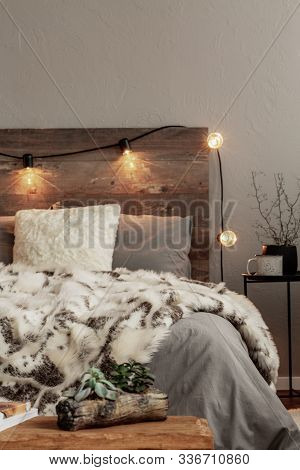 Copy Space On Empty Grey Wall Above Wooden Headboard Of Cozy Bedroom Interior