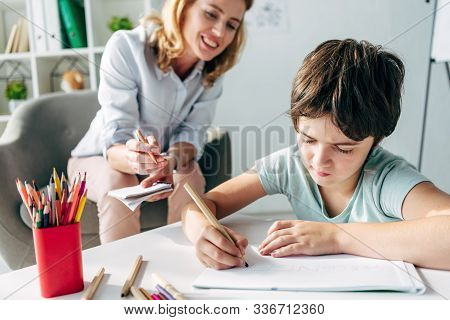 Kid With Dyslexia Drawing On Paper With Pencil And Child Psychologist Looking At It