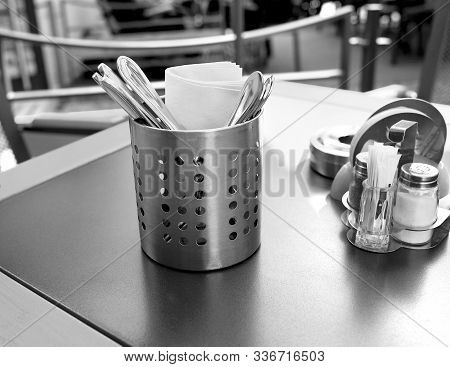 Cutlery Napkins Hodgepodge And Pepper Shaker Stand On A Table In A Restaurant