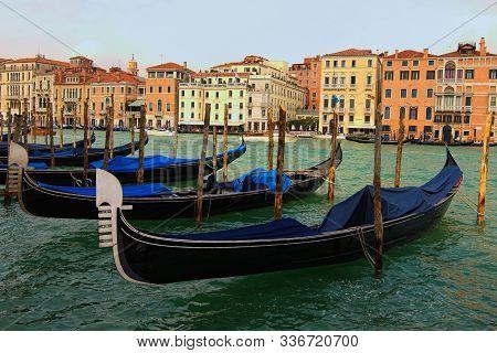 Venice, Italy-september 28, 2019: Classic Landscape Of Venice. Old Black Gondolas Moored Near Wooden