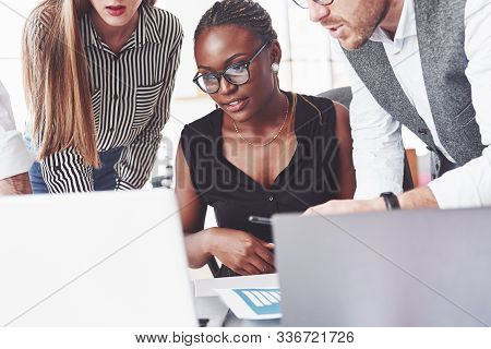 African American Woman Looking At The Laptop With Teammates. Business And Office Conception.